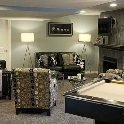 The basement features a pool table with a chandelier hanging over it to soften the decor.